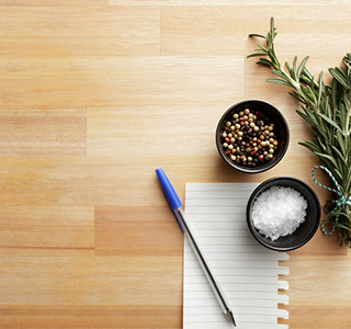 Pen and paper next to herbs and seasoning